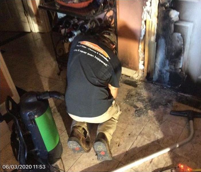 SERVPRO technician in front of entryway with fire damage
