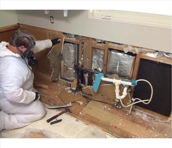 SERVPRO tech in kitchen with water damage
