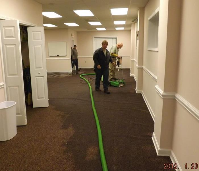 office with wet brown carpet and SERVPRO crew using an extractor